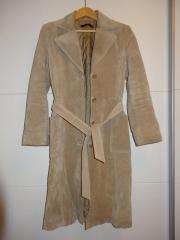 Zweireihiger Mantel aus Wildleder mit langen Ärmeln. Gefüttert sowie mit abnehmbarem Gürtel, Gürtelschlaufen und zwei Seitentaschen.